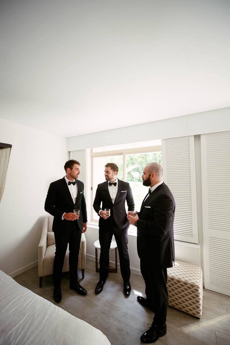 Groomsmen sharing a drink before the wedding ceremony at the Sheraton Mirage in Pt Douglas