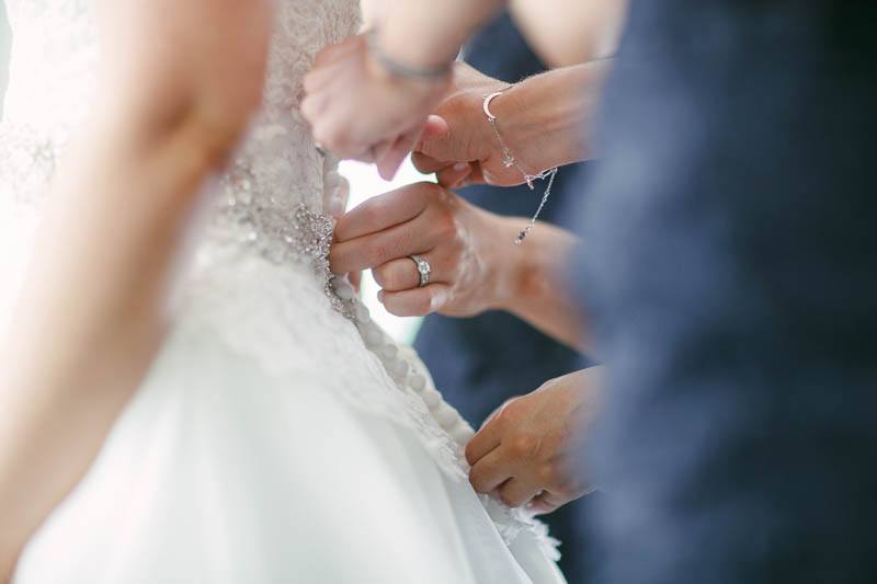 The wedding dress being done up by the bridesmaids