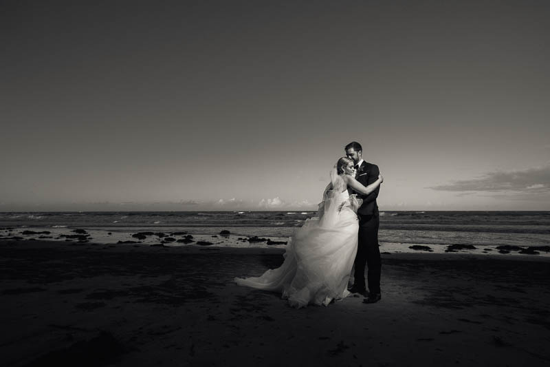 Bride and groom sharing a quiet moment on the windy beach in Pt Douglas