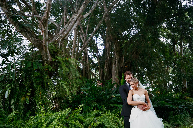 Bridal couple in front of the lush greenery at the Sheraton Mirage in Pt Douglas
