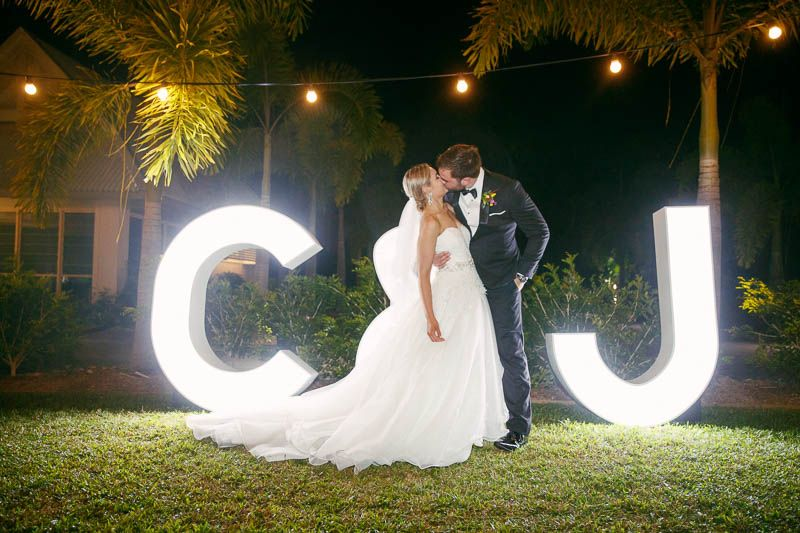 The bridal couple in front of light up letters at the wedding reception