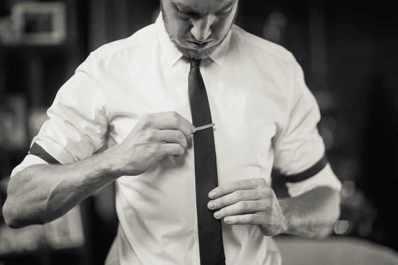 Groom putting on his tie pin before the wedding