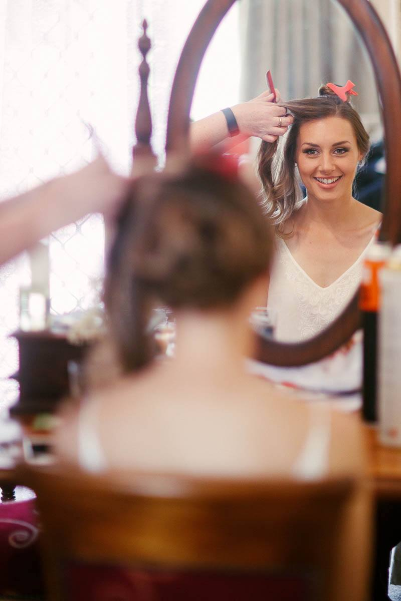 Bride looking at herself in the mirror finishing her hair