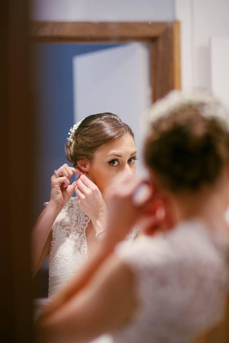Bride putting in her earrings looking in the mirror