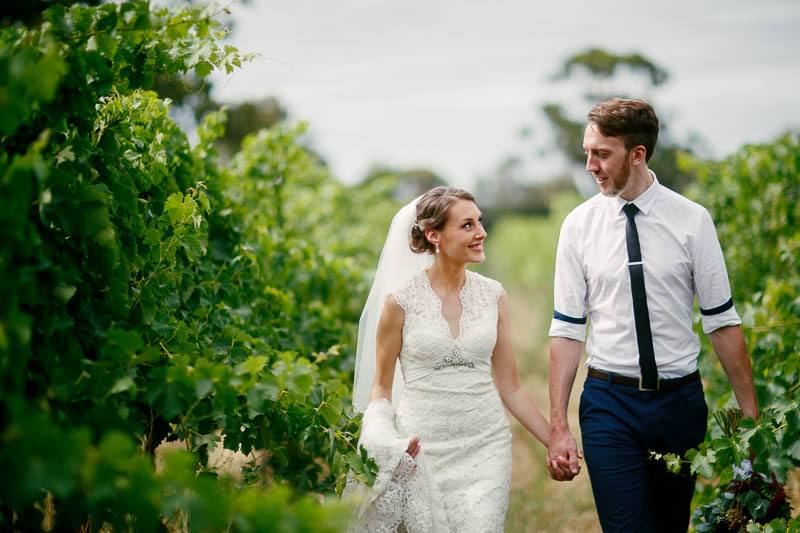 Bride and Groom walking together in the vines at Serafino Winery