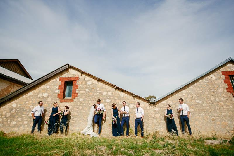 Bridal party leaning up against wall of old building in McLaren Vale