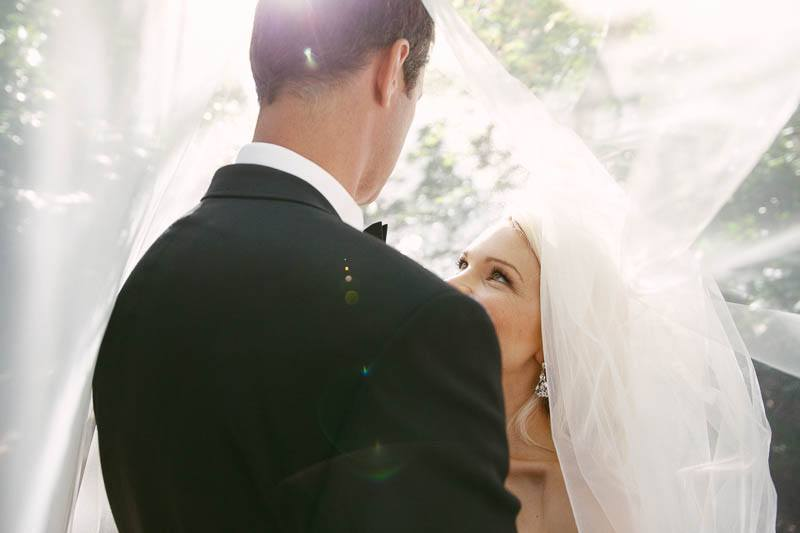 The couple stand under the bride's veil together