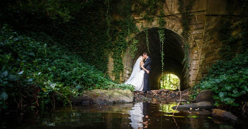 The bride and groom sharing a moment together under the bridge next door to Stangate House
