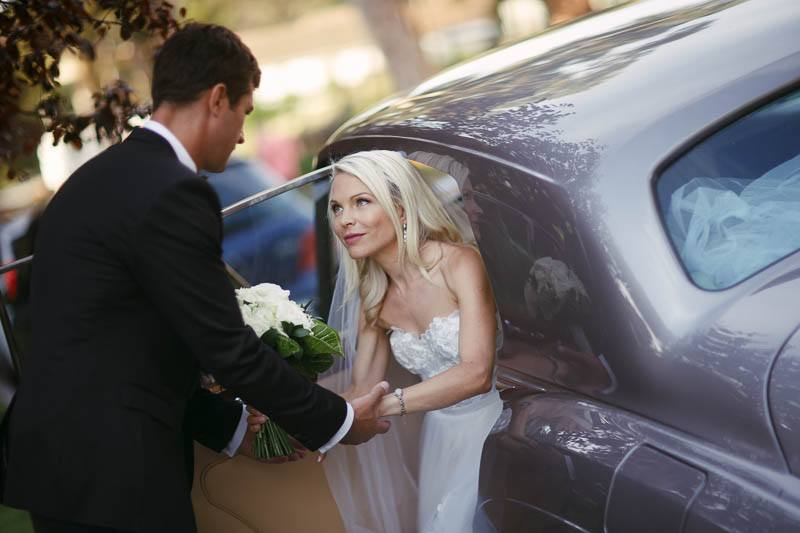 The bride getting out of the car after arriving to the reception