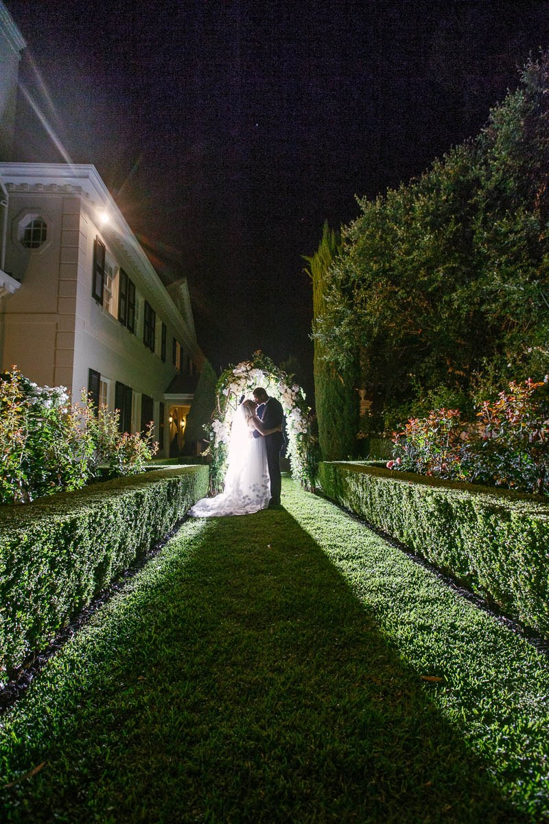 Bride and groom sneak out for some night time photos under their arch