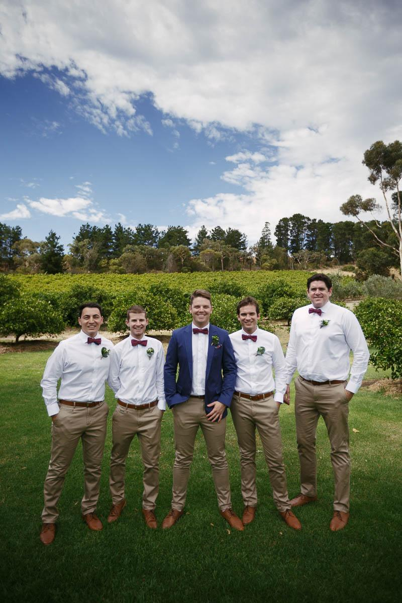 Groom and his groomsmen waiting at the front of the aisle for the bridesmaids and bride to arrive at The Currant Shed