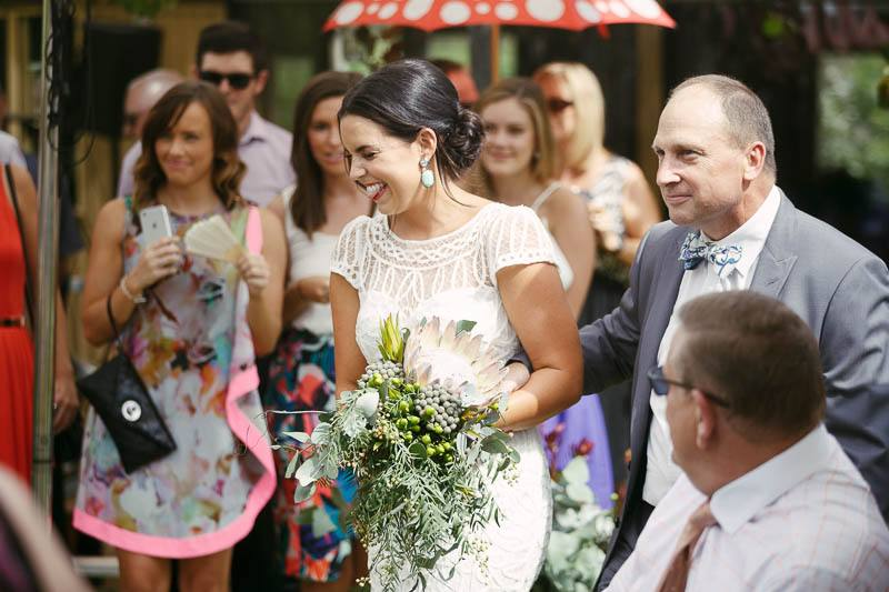 The bride laughing as she walked down the aisle with her father