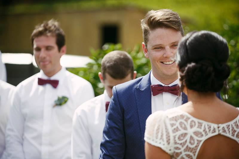 The groom smiling at his bride