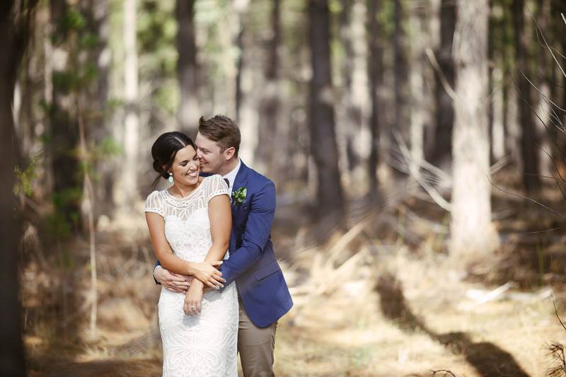 Bride and groom laughing together in a pine plantation at Kuipto Forest
