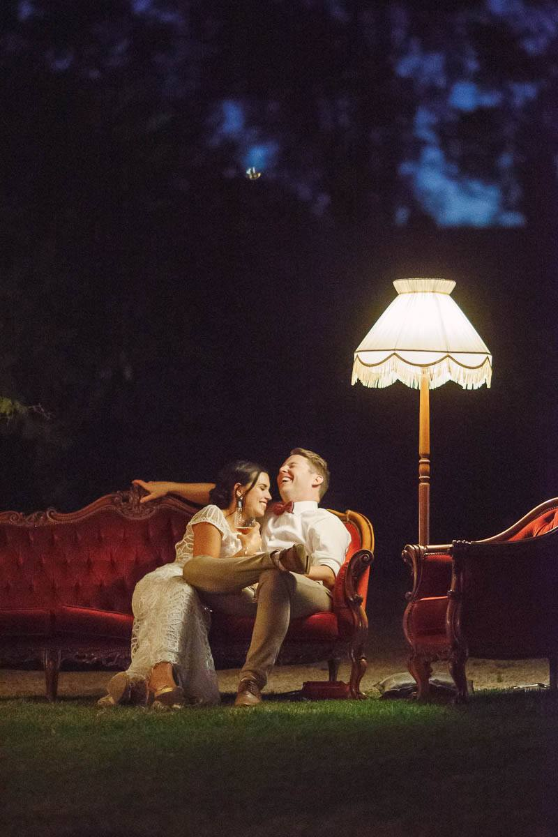 The couple sitting outside in some comfy couches at night under a lamp during the reception at The Currant Shed