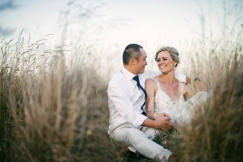 Bride and groom sitting in the long dry grass out the back of Waverley Estate just before sunset